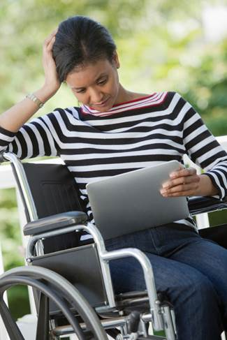 Woman in wheelchair reading a tablet