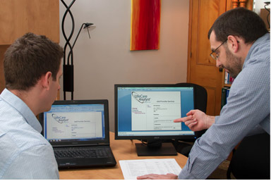 Two men looking at reports on laptops