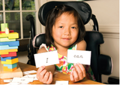Young girl in wheelchair holding two pieces of paper that spell I can