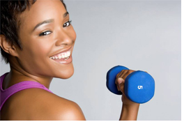 Woman smiling and holding 5 pound dumbell